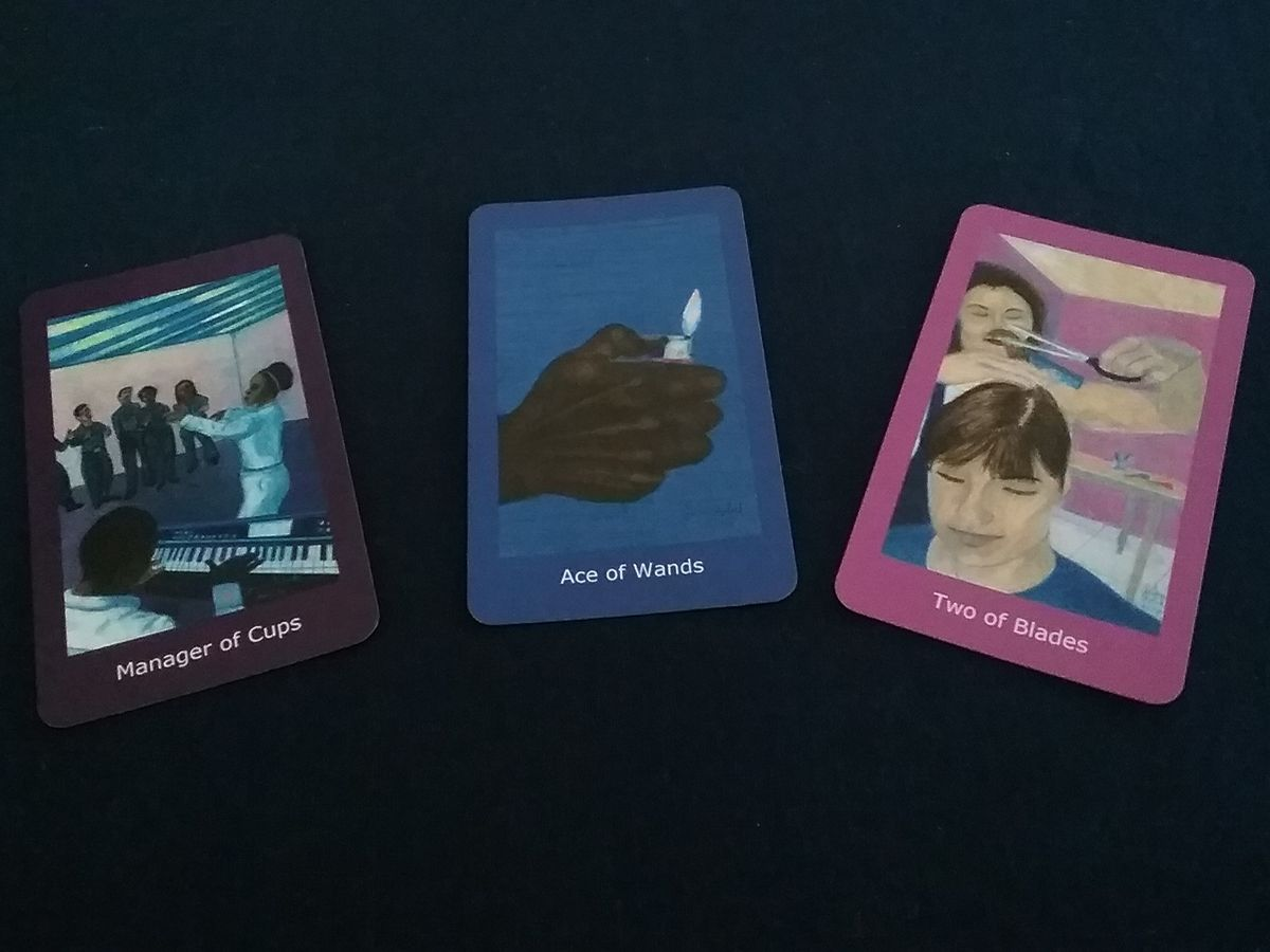 Selection of Cards 1: Three cards. Manager of cups, choir director. Ace of Wands, hand holding lighter. Two of Blades, woman cutting another woman's hair.