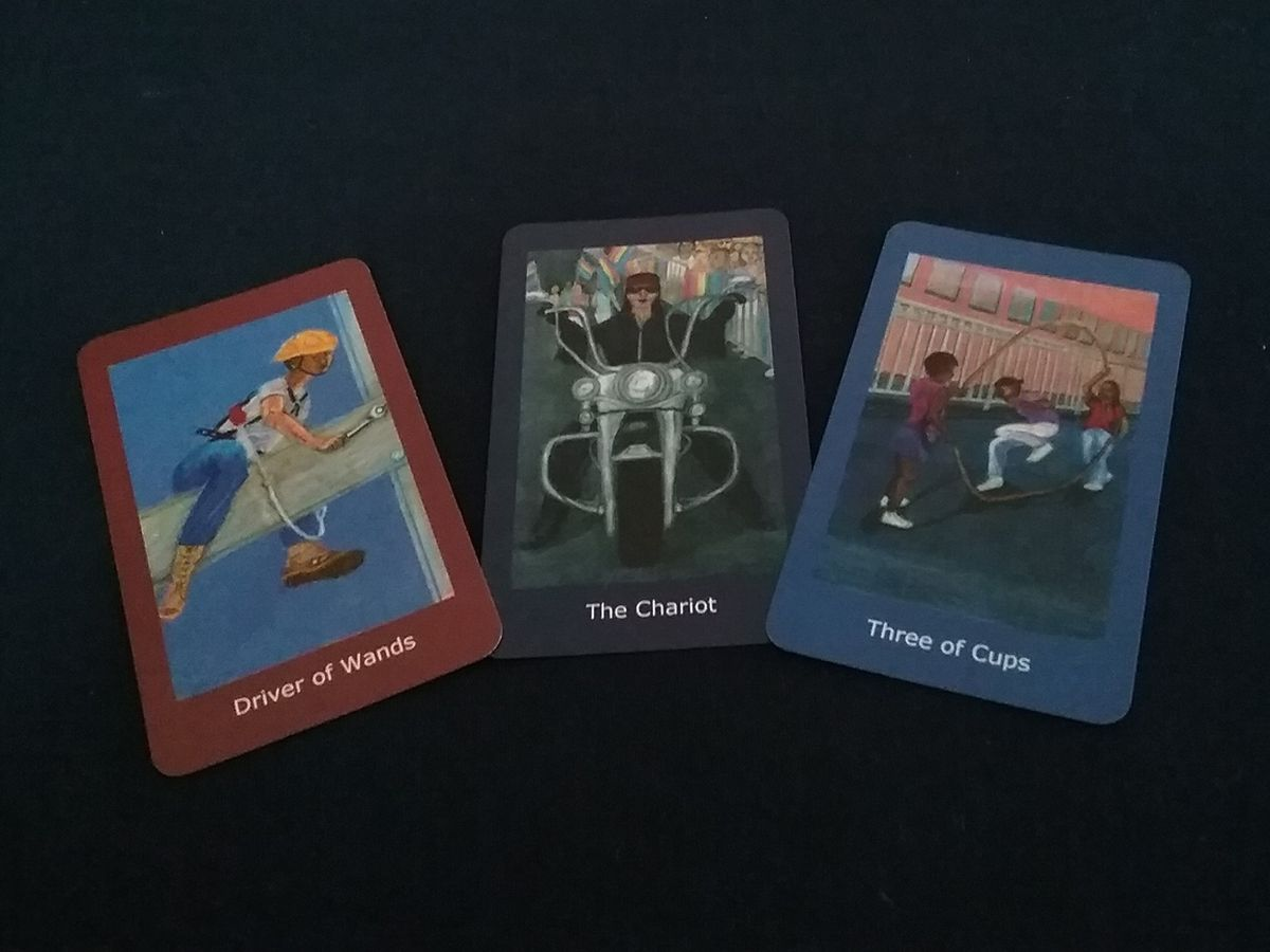 Selection of Cards 4: Three cards. Driver of Wands, construction worker astride beam. The Chariot, female biker leading pride parade, Three of Cups, three girls playing double Dutch.